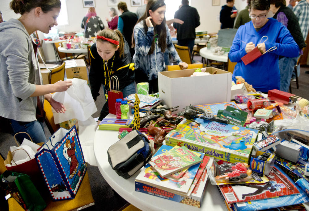 From left, Cecilia Pareja, Bri Gonzales and Martinique Sedillo, all St. Pius X students, and Annette Sedillo, right, Martinique's mother, volunteer to wrap gifts for Gift Givers Anonymous at a wrapping party at Messiah Lutheran Church in Albuquerque. The gifts will go to needy people throughout the city. (Marla Brose/Albuquerque Journal)